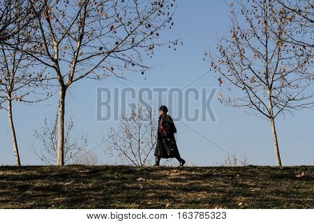Bucharest Romania 7 February 2016: A woman is walking in a park in Bucharest on a warm sunny day.