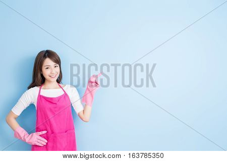 beauty housewife smile and show something to you isolated on blue background asian