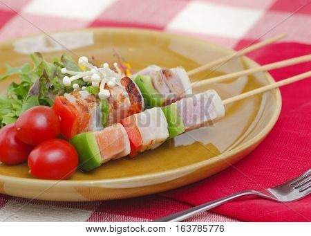 Bar-B-Q or BBQ of pork belly served with cherry tomato onion salad on skewers over brown plate.