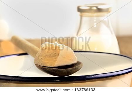 fresh yeast on a wooden spoon to be dissolved in warm milk bottle with milk in the background