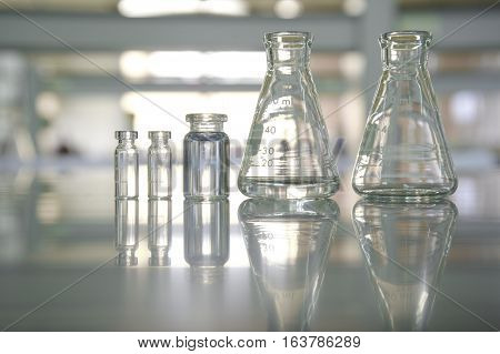 reflection clear flask and vial in science laboratory background