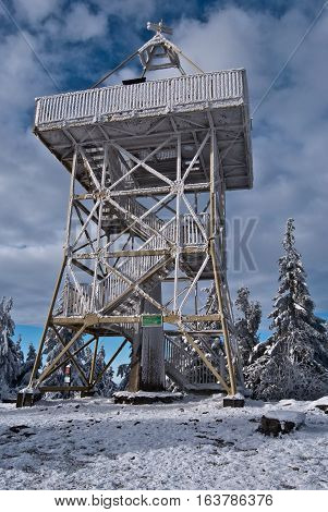 view tower on Barania Gora hill in winter Beskid Slaski mountains with snow and blue sky with clouds near Wisla resort in Poland