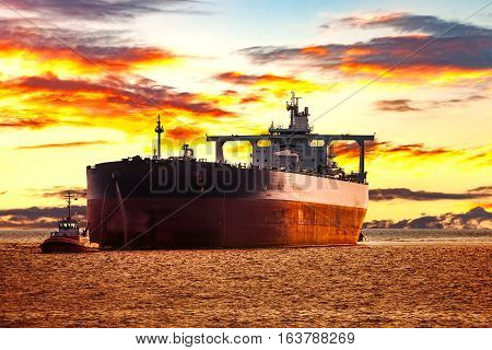 Tanker ship with escorting tugboat on sea at sunrise.