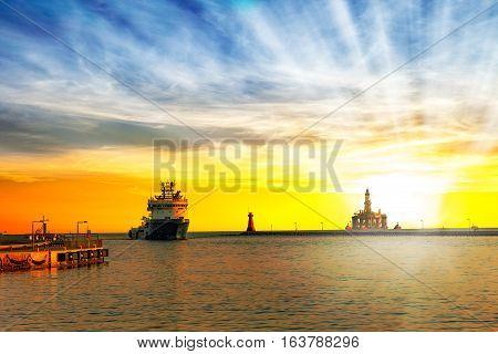 Ship return to port at sunrise .