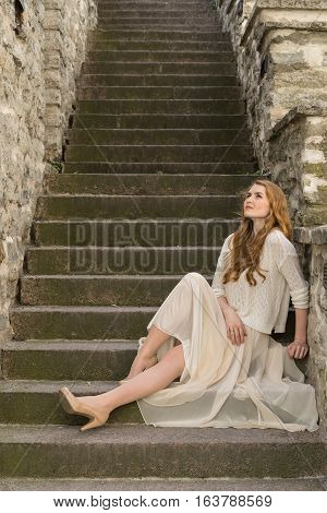 Caucasian white female model and brick stone. Beautiful girl long red hair beige skirt and cardigan. Woman siting on the stairs in old town limestone walls background