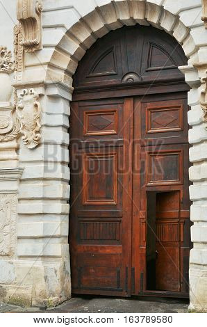 Open free path mystery peeping invitation concept. Old medieval style broun wooden door on classic facade building in Lviv Ukraine