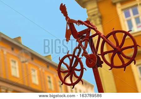 Good news information progress concept. Metal figure of postman with a red bag going up riding bike and delivering mail and newspapers. A man on his bicycle at bright sunny day. part of bicycle repair station