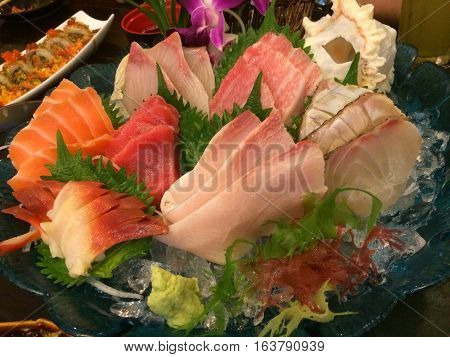 Special Deluxe Combination sashimi set Salmon Tuna maguro otoro Hotate Scallop Kanpachi Amberjack Sea Bass Sea Bream Mackerel and seaweed on ice sever with wasabi traditional Japanese food