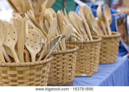 Wooden handmade cooking utensils in wooden baskets.