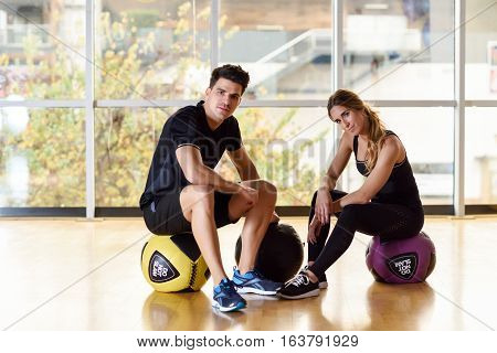 Man And Woman Sitting With Fitballs In The Gym.
