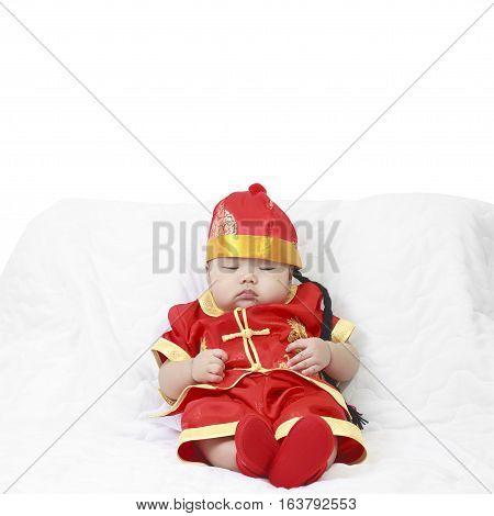 Asian baby boy wearing red Chinese suit or clothes with hat sit and sleeping lay drooling on white bed or sofa for Chinese New Year festiva in studio with copy space