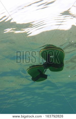 Underwater view of green flip flops floating on clear sea surface in day.