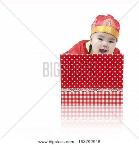Asian baby cute and smile wearing Chinese suit or clothes with hat playing and emerged from the open red gift box for surprise on Chinese happy new year day isolated on white background