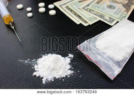 Drug addiction, syringe, money on black background.
