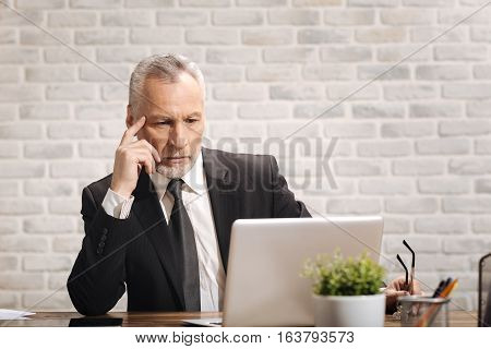 Double checking figures. Attractive concentrated senior banker looking at the document on his laptop while sitting at the desk in his office