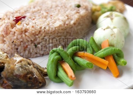 Fried rice with tamarind chili sauce fried mackerel carrot yardlong bean thai eggplant and acacia pennata omelette on white dish and wood table for thai food background