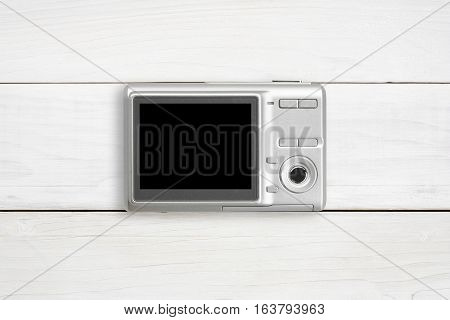 silver digital compact camera with blank black screen display place on center white vintage wood table and top view with copyspace