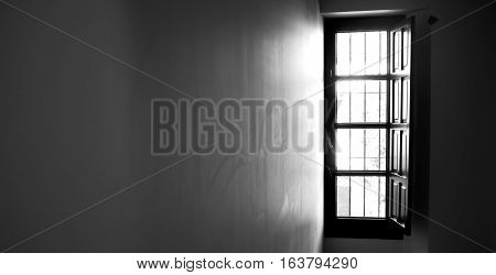 Light coming through a window and reflecting into the wall of a room, black and white, long horizontal.