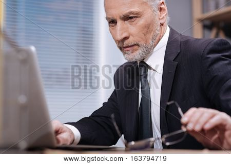 I can barely see it. Focused handsome mature businessman reading something on his computer and trying to put on his glasses while sitting at the desk in his office
