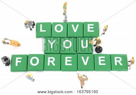 Miniature worker team building word love you forever on white background
