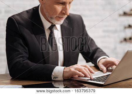Summing up year work. Handsome concentrated senior office worker typing a document on his laptop while sitting at the table in his office