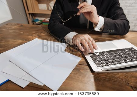 Right to the next page. Well dressed slim qualified executive looking through a document using his laptop while sitting in his office