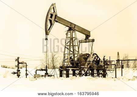 Pump jack and wellhead in the oilfield. Rig at the background. Oil and gas concept.
