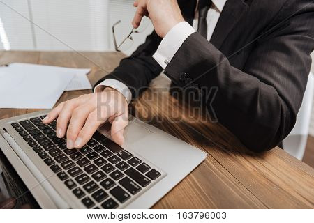 Correcting some points. Handsome focused senior executive rewriting some articles of the document using his laptop while sitting at the table in his office