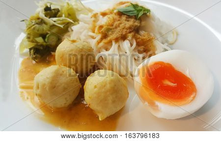 Vermicelli solution (Noodles) and fish curry coconut milk with vegetable on white background.(Kanom Jeen Nam Ya)