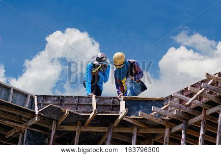Construction workers collaborating in the installation of cement formwork frames.