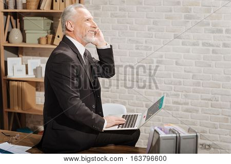 I believe in this project. Attractive joyful senior businessman calling his financial partner and holding his laptop while sitting on the table in his office