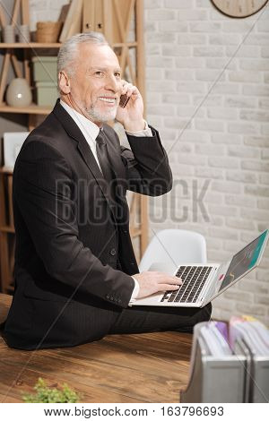 My start up is ambitious. Handsome excited mature gentleman talking on the phone with his financial advisor while holding his computer and sitting on the table at his office
