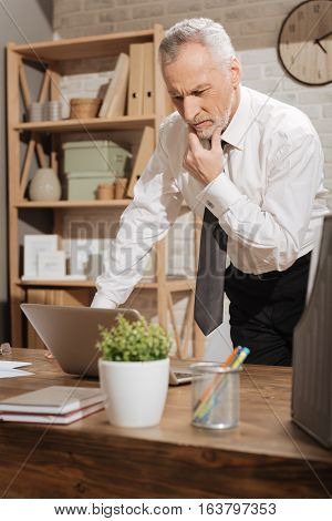 Seems bad for me. Upset emotional senior man looking at the screen of his computer while reading some news and standing at the table in his office