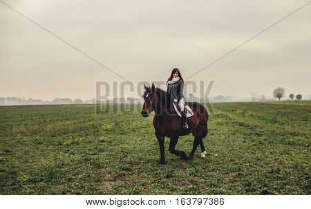 Beautiful girl riding a brown horse at landscape
