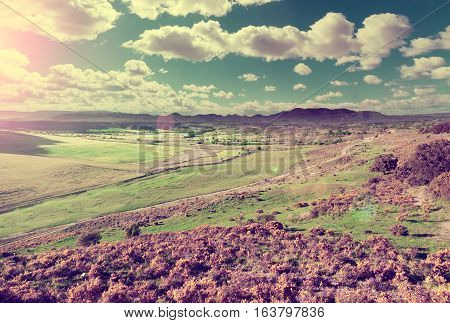 Green grass and hill.Blue sky and mountain panorama in retro style.