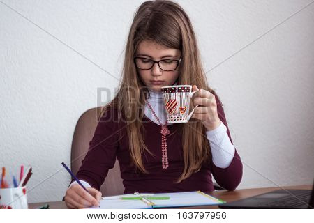 Beautiful Cute Little Blond Girl With Glasses And Purple Dress Behave Serious And Take Notes In Her