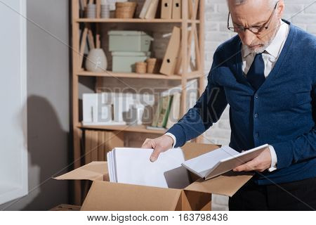End of the career. Concerned handsome elderly man looking through his notes while packing things after being fired
