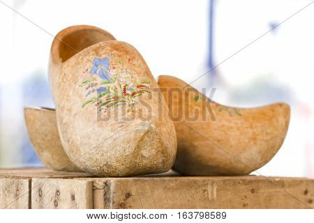 A pair of wooden clogs on a wooden surface.