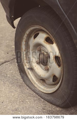 Close up shot of a car with a flat tire.