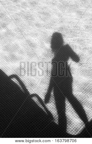 One armed shadow of a woman by the swimming pool, in black and white.