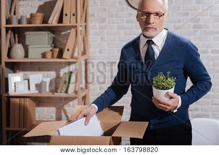 Where do I go from here. Thoughtful concerned elderly businessman putting away his things after being fired while holding some objects from his office