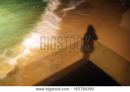 Lonely shadow of woman on veranda by the sea shore.