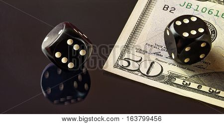 On the mirror surface reflects the black dice to play poker and is a banknote fifty dollars.