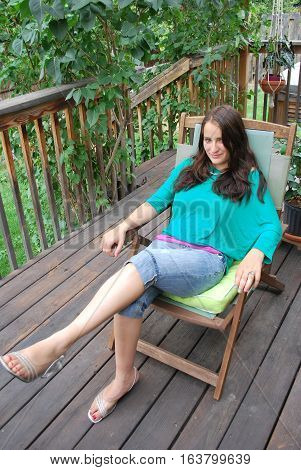 Female beauty relaxing alone on patio deck outdoors.