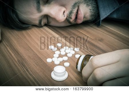 Depressed Man Commiting Suicide. A Lot Of Pills Spilled On Table