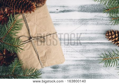Gift wrapped craft paper with pine cones and fir branches on the wooden shabby chic table, top view, copy space at the right