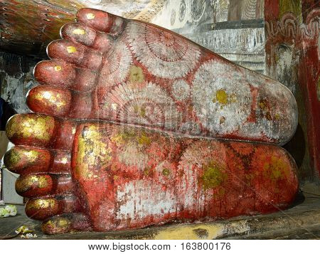 Feet of reclining buddha in ancient Buddhist complex in Dambulla cave temple. Sri Lanka. The photograph is presenting the statue of Buddha