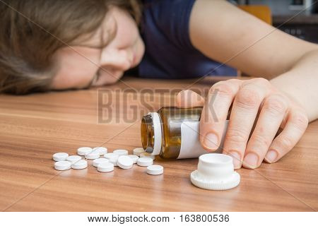 Young Woman Is Lying On Table With A Lot Of Pills Spilled. Overd