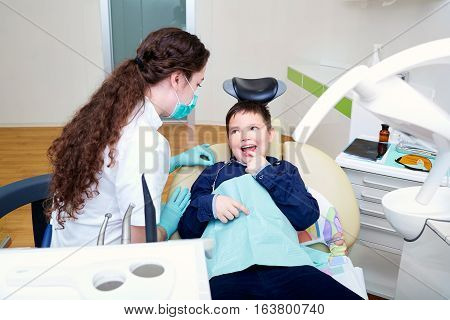 The child in dentist's chair with a female doctor.