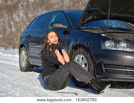 Sexy helpless woman sitting near broken car in winter